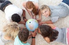 Adolescenti sul pavimento che esaminano un globo Fotografia Stock