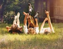 Adolescenti trascurati che si trovano sul prato inglese verde con la chitarra Fotografia Stock