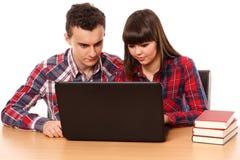 Adolescents étudiant ainsi qu'un ordinateur portable Image libre de droits