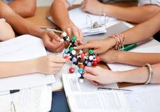 Adolescents étudiant des molécules dans une bibliothèque Image stock