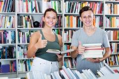 Adolescents achetant de nouveaux livres et montrant des pouces  Photographie stock libre de droits