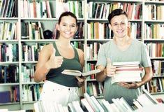 Adolescents achetant de nouveaux livres et montrant des pouces  Images libres de droits