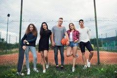 Adolescents attirants au terrain de jeu avec le basket-ball Photos libres de droits
