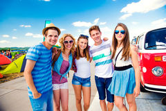 Adolescents au festival de musique d'été par campervan rouge de vintage Photo stock