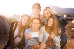 Adolescents au festival de musique d'été, prenant le selfie avec le smartphon Photographie stock libre de droits