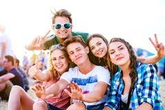 Adolescents au festival de musique d'été, se reposant au sol Photos stock