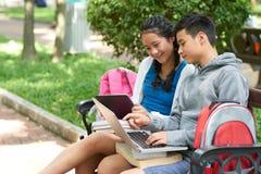 Adolescents avec des dispositifs se reposant sur le banc photo libre de droits