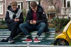 Adolescents avec des téléphones portables Image libre de droits