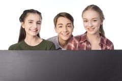 Adolescents avec la bannière vide d'isolement sur le blanc Photographie stock libre de droits
