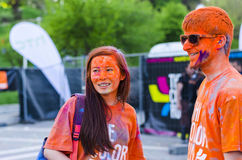 Adolescents avec la poudre orange à la course de couleur Photographie stock libre de droits
