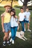 Adolescents avec le chien en parc Image stock