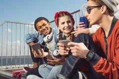 Adolescents ayant l'amusement avec des smartphones dans le parc de planche à roulettes Photos libres de droits