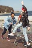 Adolescents ayant l'amusement avec le caddie et la bicyclette Photographie stock libre de droits