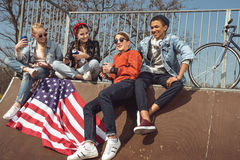 Adolescents ayant l'amusement avec le drapeau américain dans le parc de planche à roulettes Photographie stock libre de droits