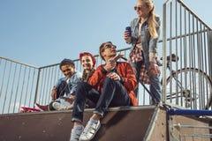 Adolescents ayant l'amusement avec le smartphone dans le parc de planche à roulettes Photographie stock libre de droits