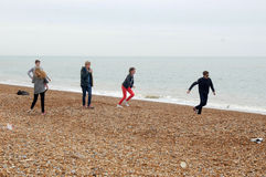 Adolescents ayant l'amusement sur la plage de Hastings Photo libre de droits