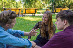 Adolescents causant en parc se reposant dans l'herbe photos libres de droits