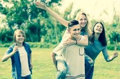 Adolescents courant par la pelouse verte en été en parc Photographie stock libre de droits