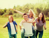 Adolescents courant sur la pelouse verte en parc Images stock