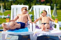 Adolescents détendant sur des lits pliants dans le waterpark Photographie stock