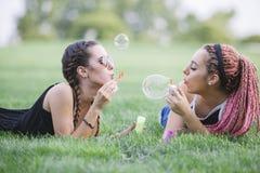 Adolescents de hippies jouant avec des bulles sur le parc Photo stock
