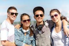Adolescents de sourire dans des lunettes de soleil accrochant dehors Photographie stock libre de droits