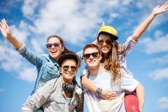 Adolescents de sourire dans des lunettes de soleil ayant l'amusement dehors Photo stock