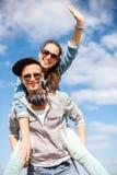 Adolescents de sourire dans des lunettes de soleil ayant l'amusement dehors Images stock