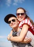 Adolescents de sourire dans des lunettes de soleil ayant l'amusement dehors Photo libre de droits