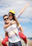 Adolescents de sourire dans des lunettes de soleil ayant l'amusement dehors Photographie stock libre de droits