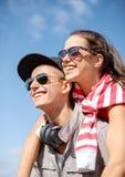 Adolescents de sourire dans des lunettes de soleil ayant l'amusement dehors Images libres de droits