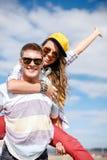 Adolescents de sourire dans des lunettes de soleil ayant l'amusement dehors Photos libres de droits
