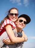 Adolescents de sourire dans des lunettes de soleil ayant l'amusement dehors Image stock