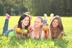 Adolescents en bonne santé avec des fruits dans l'herbe Images stock