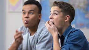 Adolescents enthousiastes mangeant du maïs éclaté et observant le drame tendu de crime sur TV par câble clips vidéos