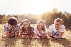 Adolescents et concept de vacances Les jeunes heureux se trouvent sur l'herbe verte, ont des sourires positifs, utilisent les tél Photographie stock libre de droits