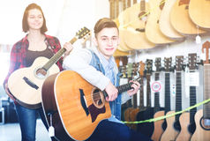 Adolescents examinant des guitares dans la boutique Photos libres de droits