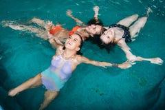 Adolescents féminins drôles dupant autour dans la piscine riant et appréciant leurs week-ends Image libre de droits