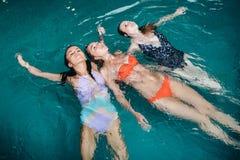 Adolescents féminins drôles dupant autour dans la piscine riant et appréciant leurs week-ends Photo stock