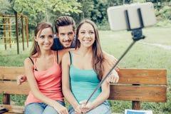 Adolescents gais prenant des selfies avec un selfie-bâton Photographie stock