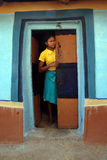 Adolescents Girl in rural India. June 02,2011 Rampurhut,Birbhum,West Bengal,India,Asia- A adolescent girl peeping through a colorfull door in a tribal village of royalty free stock image
