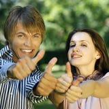 Adolescents heureux affichant le signe EN BON ÉTAT Photos stock