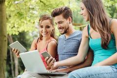 Adolescents heureux au parc utilisant des périphériques mobiles Photographie stock