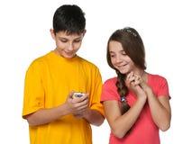 Adolescents heureux avec un téléphone portable Photographie stock libre de droits
