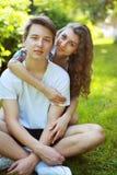 Adolescents heureux de couples de portrait s'asseyant sur l'herbe en été Image stock