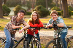 Adolescents heureux et fille ayant l'amusement sur des bicyclettes Image stock