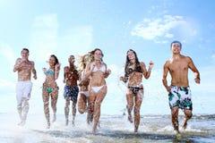 Adolescents heureux jouant à la mer Photo stock