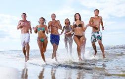 Adolescents heureux jouant à la mer Photographie stock