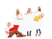 Adolescents heureux tenant des indicateurs et une bannière Images stock
