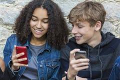 Adolescents hommes-femmes de fille de garçon à l'aide du téléphone portable Image stock